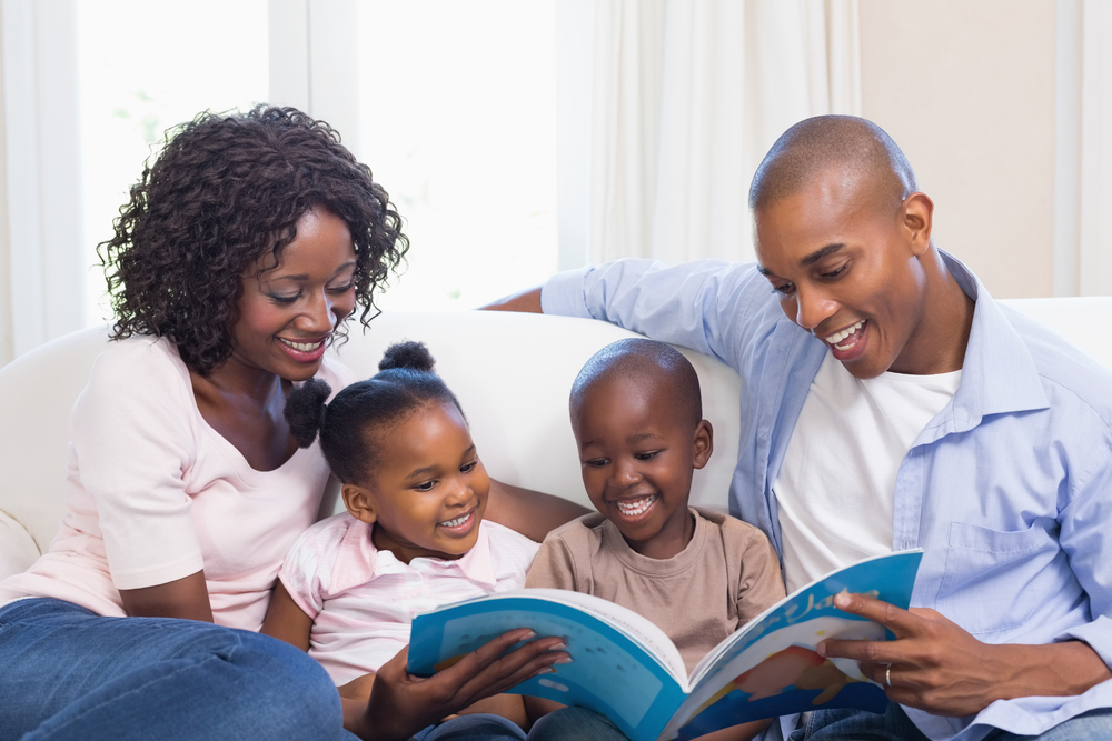 Happy family on the couch reading storybook at home in the living room-1