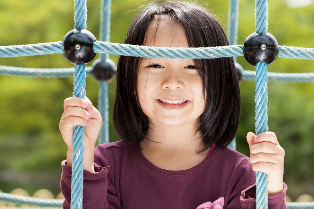 Smiling asian girl on a playground, horizontal